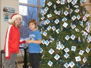 Emma Carswell, in Grade 5, and Zoey Britton, Grade 2, flip the switch on this year's Christmas Wish Tree at Winchester District Memorial Hospital. Zandbergen photo, Nation Valley News